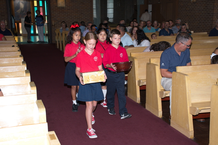 The children bringing up the gift for the children's mass