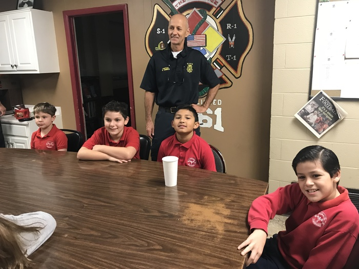 Fifth grade boys enjoying breakfast with the fire men